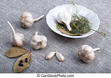 Garlic and spices on a gray fabric background