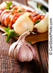 Garlic bud on old wooden board in front of skewers
