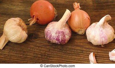 Garlic bulbs and onion on wooden board, natural medicine,...