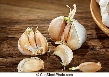 Garlic close up on wooden plate on rustic background, shallow depth of field, selective focus, macro