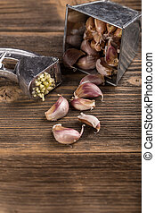 Garlic clove and press on rustic wooden background