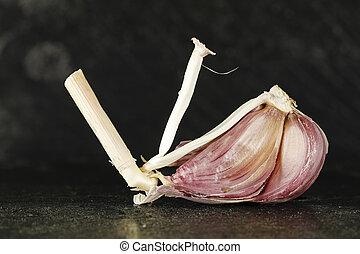 Garlic clove - Fresh garlic as a dish ingredient on a dark...