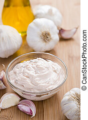 Garlic Dip (Aioli) with ingredients on wooden background