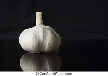 Garlic head over a reflective surface against a black ...