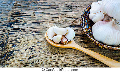 garlic in wooden spoon and basket place on old wooden background