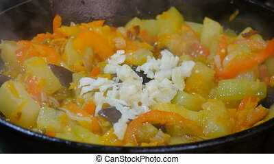 Garlic is added to the vegetable stew, stirred with a wooden spoon.