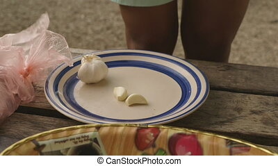 Garlic on Plate Sitting on Table - Handheld, medium close up...