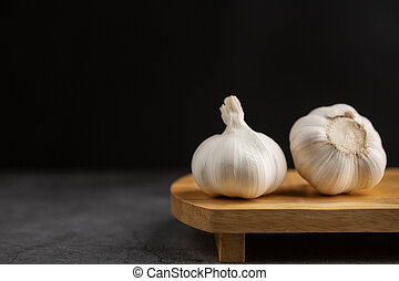 Garlic on the black cement floor and black background.