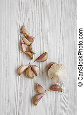 Garlic on white wooden background, overhead view. From above, flat lay. Copy space.