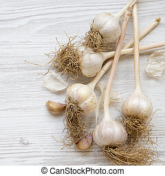 Garlic on white wooden background, view from above. Top view, overhead.