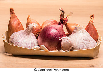 garlic onion shallots in a small wooden basket