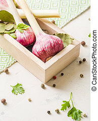 Garlic purple with Parsley in wooden box on a white stone background.