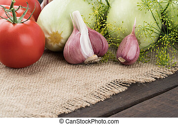 Garlic, tomatoes, zucchini on the old wooden table.