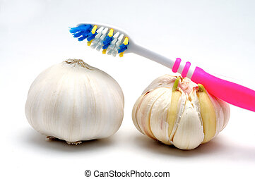 Garlic - Toothbrush and garlic on a white background