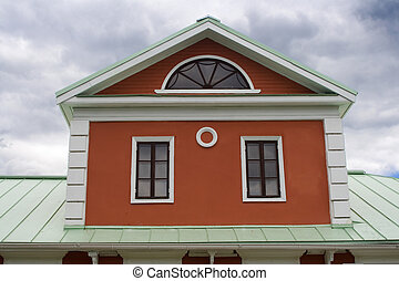 Garret of historical house with three windows on green metal roof. Tsaritsyno, Moscow.