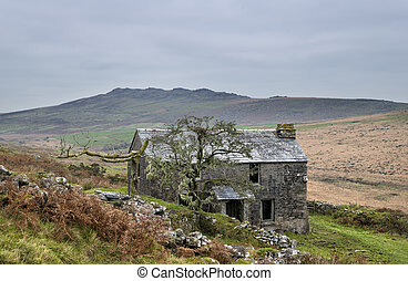 Abandoned farm house on Garrow Tor a remote part of Bodmin Moor in Cornwall, with Brown Willy in the background