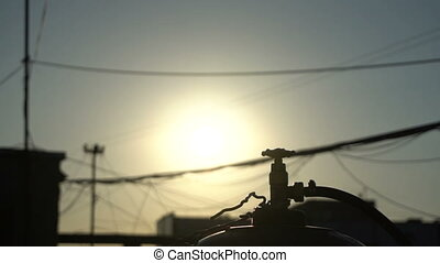Gas cylinder on the roof at sunset. Slow motion