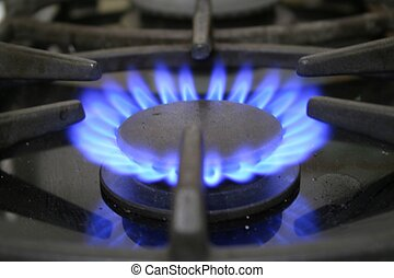Close up of gas hob with blue flame.