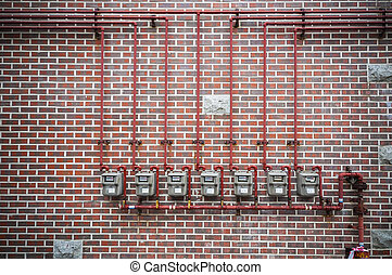 Gas meters and pipe on brick wall