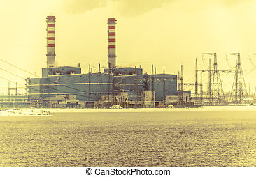Gas power plant. Pipes with smoke. Lake with fog foreground.
