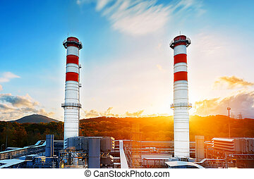Gas Power Plant with two long pipes of white color with red poloskai on the background of mountains and sunrise in a picturesque environmentally clean place.