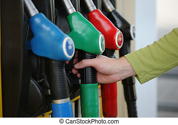 Gas pump - Closeup of male hand holding gas pump nozzle at...