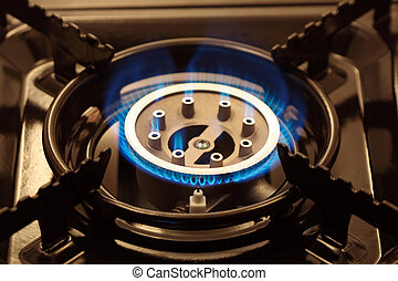 Closeup of black portable gas range with blue flame
