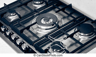 Metallic gas range with knobs and rings.