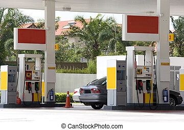 Image of a gas station with a motorcar being refulled.