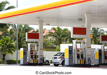 Image of a gas station with cars being refulled.
