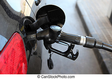 Gas station pump nozzle in the cars fuel tank