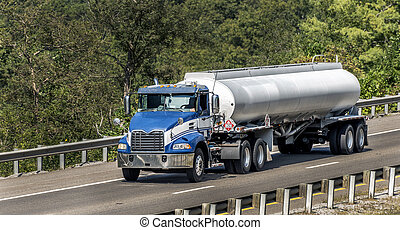 Horizontal shot of a Blue Gasoline Tanker Truck On The Interstate.