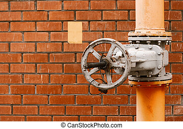 Gas valve on yellow natural gas distribution industrial pipe in front of red brick wall with copyspace