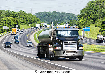 A gasoline tanker leads traffic down the interstate. Note: All logos and identifying marks have been removed from all vehicles. Image was created on hot day, so heat waves from the asphalt create some distortion, especially on vehicles farther from the camera, enhancing the long telephoto effect.