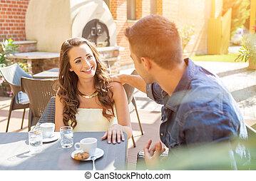gasthaus, essende, paar, junger, sprechende , während, terrasse