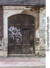 Gate of an old devastated building sprayed with graffiti...