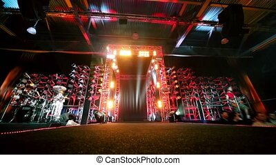 Gate of metal constructions with colorful illumination, guitarist and drummer on sides