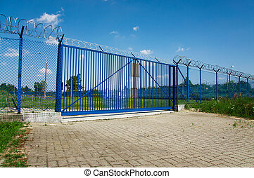 gate  - big blue gate with barbed wire