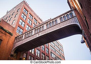 Gateway bridge between two red brick buildings in Chelsea - ...