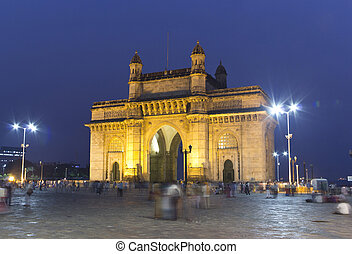 night at Gateway of India monument in downtown Mumbai, Bombay. People walking and resting in front of India Gate Memorial