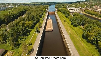 Sluice Gates on the River. Aerial view barge, ship in the river gateway. River sluice construction, water river gateway. Shipping channel. 4K, flying video, aerial footage