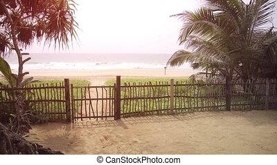 Simple gate and sandy path separates a villa compound from the tropical beach paradise just a few steps away. Full HD footage