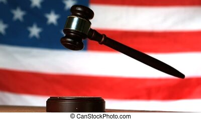 Gavel dropping on sounding block with american flag in background in slow motion