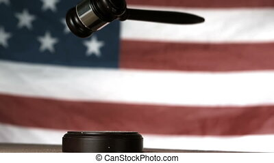 Gavel dropping onto sounding block with american flag in background in slow motion