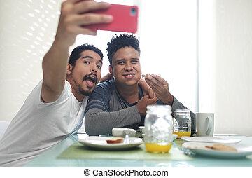 Gay Couple Eating Breakfast Taking Selfie With Phone