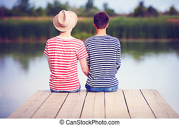 gay couple in love sitting on river bank