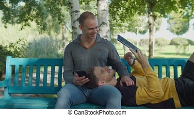 Gay couple relaxing with digital devices outdoors
