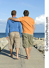 Gay couple walking on pathway along by the beach.