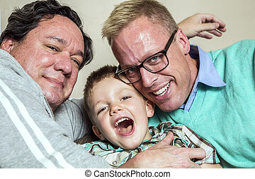 Gay Couple with Young Son - Two gay men hug their happy...