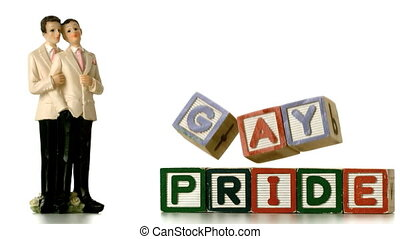 Gay groom cake toppers beside blocks falling and spelling...